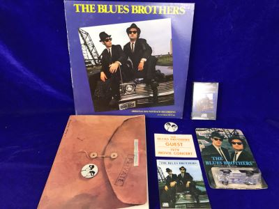 Vintage 1980 The Blues Brothers Movie Memorabilia Lot: Promo Vinyl Record, Sealed Cassette Tape, Button, 1979 Movie Concert Sticker, Blues Brothers Album Sticker, Bluesmobile Die-Cast Metal Replica Car On Damaged Card, And Private Perigee Book