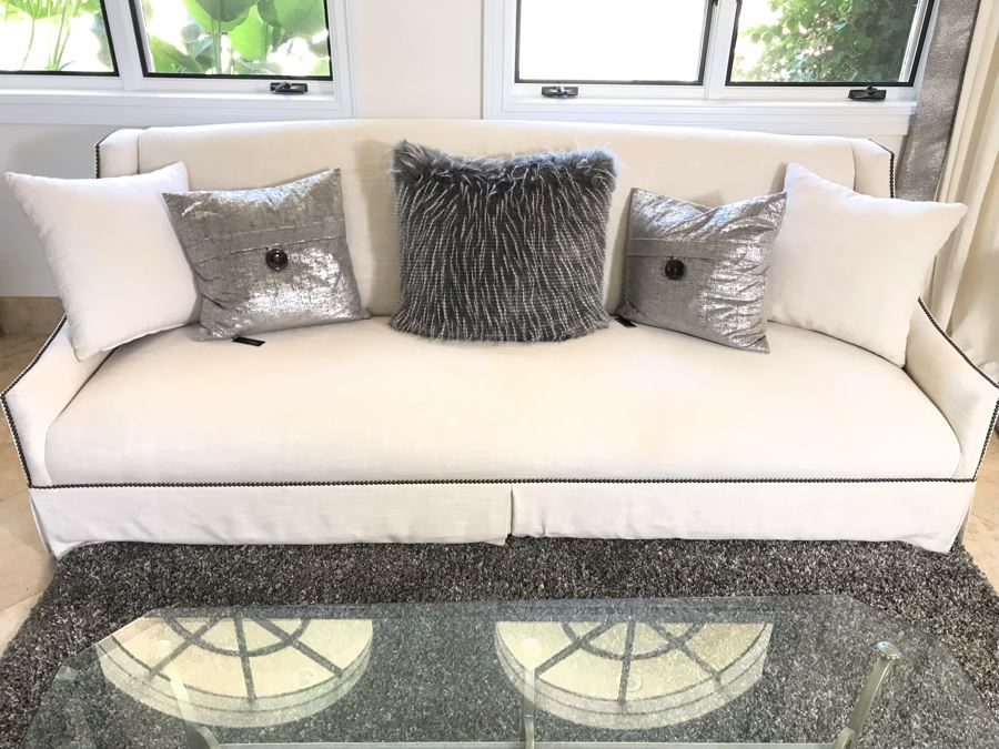 Classy Contemporary White Cream Sofa With Brass Nailheads And Five Throw Pillows 8'W X 37'D X 35'H [Photo 1]